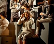 Jongeren, gekleed in het grijs, staan op podium