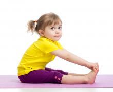 Meisje strekt haar benen op yogamat