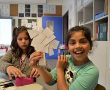 Meisje toont haar zelfgemaakte boom van papiersnippers