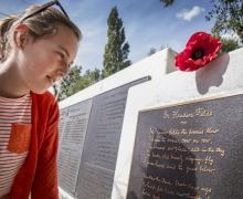 Vrouw leest gedicht 'In Flanders Field' dat op graf staat