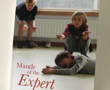 Boek cover van 'Mantle of the Experts: drama als leermiddel in het lager onderwijs, een handleiding voor beginners' van Bob Selderslaghs en Tim Taylor. Op de cover spelen 3 jongetjes toneel.