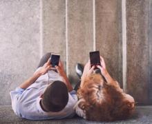 Bovenaanzicht van man en vrouw die op smartphone bezig zijn