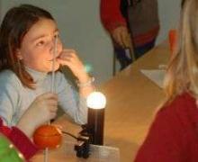Kind zit aan tafel achter een lamp