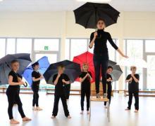Volledig in het zwart gekleed, staan enkele leerlingen onder paraplu's