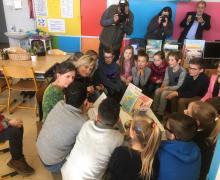 Hilde Crevits leest samen met kinderen boeken in de klas