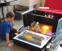 Jongen speelt met theaterkoffer