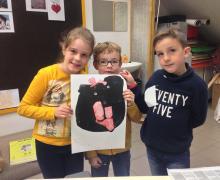 3 kinderen houden hun zelfgemaakte illustratie vast. Illustratie is een zwart figuur met rode kledingstukken.