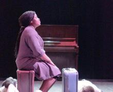 Op het podium zit meisje op een koffer. Naast haar liggen leerlingen neer.
