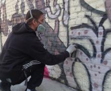 Leerling spuit graffiti op muur