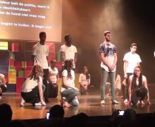 Jongeren staan op het podium. Ze hebben allemaal een wit t-shirt aan.