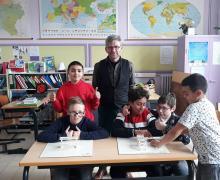Leerlingen en Bart Baccarne tonen in klaslokaal trots hun designs voor de speelplaats