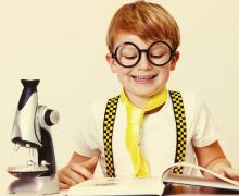Jongen met grote rond zwarte bril, een gele das en bretellen aan leest in een boek. Op tafel ligt ook een microscoop.