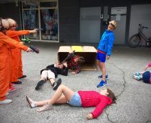 3 kinderen in oranje rally overall houden andere kinderen onder schot met nep pistolen