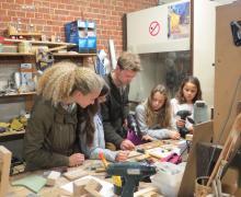 Leerlingen maken instrumenten in atelier van Piet Decalf