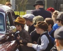 Kinderen gekleed in ouderwetse kleren kijken door venster van oldtimer