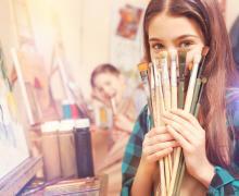 Meisje houdt verfborstels voor gezicht vast
