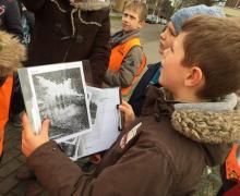 Kind met kopie van Réné Simons' schilderij in de hand, luistert aandachtig naar uitleg
