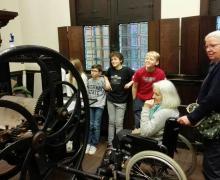 Leerlingen en bewoners van het woonzorgcentrum Vinck-Heymans kijken naar grote drukpers in Museum Plantin-Moretus