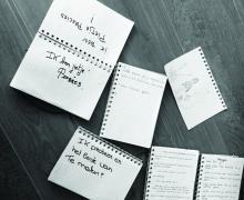 Verschillende notitieboekjes met tekeningen en tekst. Zo staat er op een notitieboekje 'Ik ben een pietje precies'. Op een ander notitieboekje staat 'Ik probeer er het beste van te maken'. Een ander papiertje heeft de vragen 'Welke droom zou je nog vervullen?' en 'Wat is het leukst aan oud worden?'.