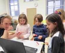 Enkele kinderen kijken samen met Jochem naar beelden op de laptop
