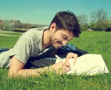 Jongeman schrijft in notitieboekje terwijl hij in het grasveld ligt