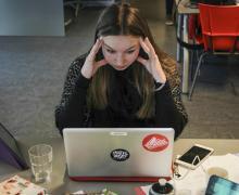 Meisje kijkt gestresseerd naar laptopscherm