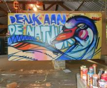 Kleurrijke graffiti zwaan op een plaat. Naast de zwaan staat 'Denk aan de natuur' in graffiti letters gespoten.