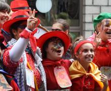 Leerlingen verkleed in rode kostuums (als murga's)