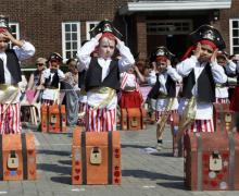Kinderen verkleed als piraten staan op de speelplaats met zelfgemaakte schatkisten