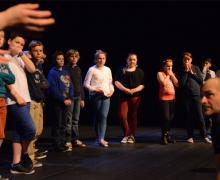 Op het podium luisteren leerlingen aandacht naar uitleg