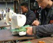 Leerlingen naaien met naaimachine