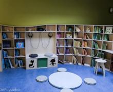 Bibliotheek met rekken vol boeken, koptelefoons om audioboeken te beluisteren en in het midden een zitplaats waar de kinderen kunnen lezen