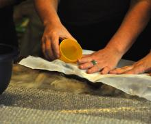 Handen maken een textielkunstwerk