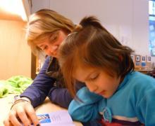 Student leest boek voor aan kind