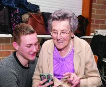 Oudere vrouw en jongen kijken naar smartphone