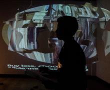 Voorstelling tijdens de expo met een beeld geprojecteerd op de witte jassen die in de zaal hangen.