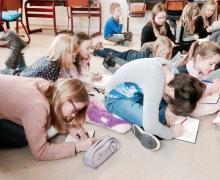 Kinderen liggen en zitten op de grond terwijl ze in hun notitieboekjes schrijven