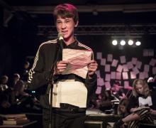Jongen leest gedicht voor op podium