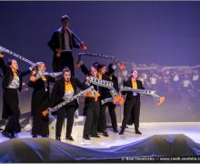 Leerlingen zwaaien met sjaals op podium