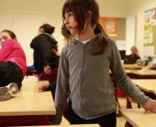 Kinderen dansen op banken in klaslokaal