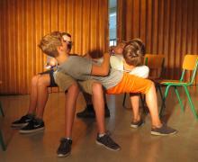 4 leerlingen vormen samen een menselijke tafel door op elkaar te leunen