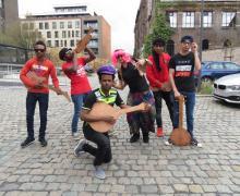 Verklede leerlingen uit de post-OKAN klas bespelen uit hout gesneden instrumenten