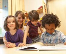 3 kinderen en een juf lezen een boek