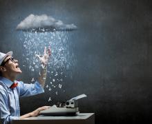 Man typt op typmachine terwijl een wolk boven hem letters op zijn werk regent