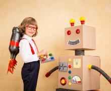 Jongen verkleed als professor met een jetpack gemaakt uit colaflessen op zijn rug, bestuurt zijn zelfgemaakt robot.