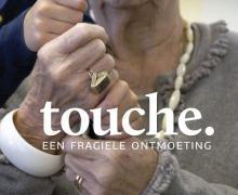 Poster voor 'Touche: een fragiele ontmoeting'. Een oudere vrouw houdt de handen vast van een kind.
