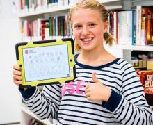 Meisje poseert met Bibit-app in bibliotheek.