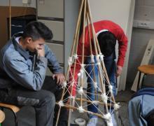 Leerlingen van bso maken een tipi tent met hout