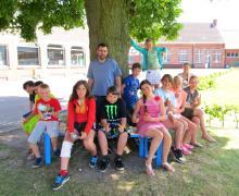 Leerlingen en Dries Warlop zitten op een bankje rond boom