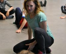 Danseres Judith Clijsters zit neer tussen leerlingen